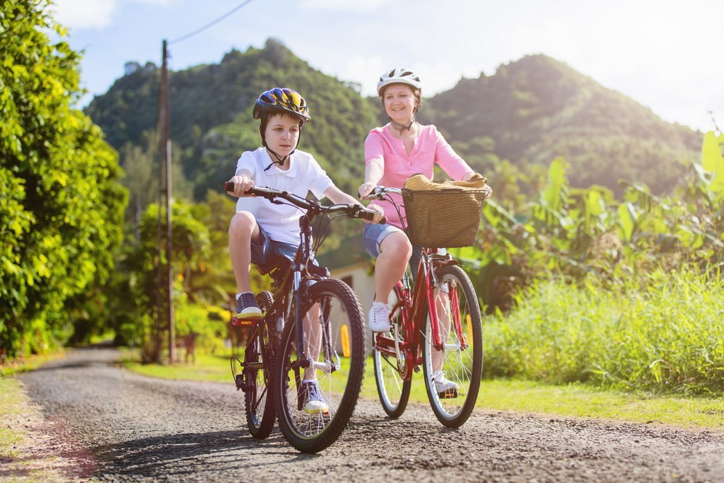 Family of mother and son biking at tropical settings having fun together
