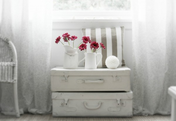 suitcase-stack-beneath-window-with-crimson-florals-in-jugs-600x412